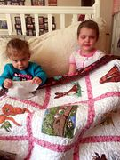 Jocelyn H. and her sister with her quilt